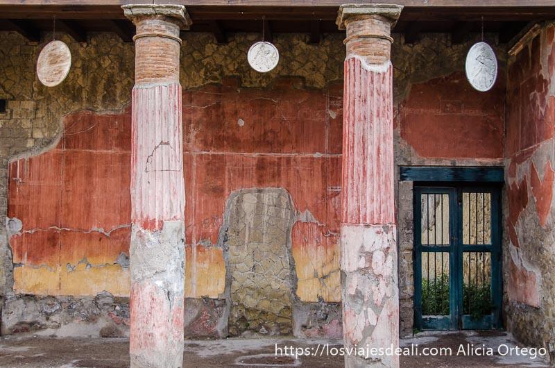 patio con columnas y pared roja visita a herculano