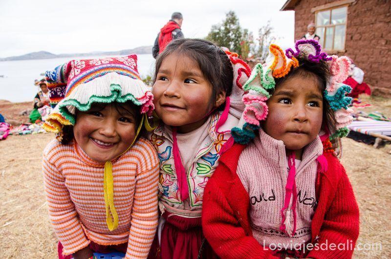 tres niñas de península de capachica vestidas con gorros de lana de colores sonríen a la cámara portada de guías de viaje de América
