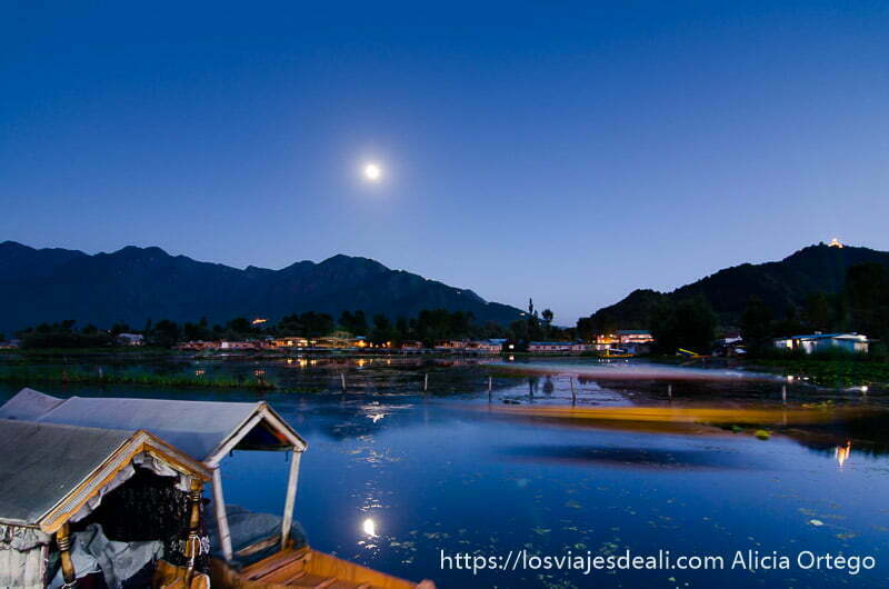 lago dal a la luz de la luna con una barca pasando delante srinagar