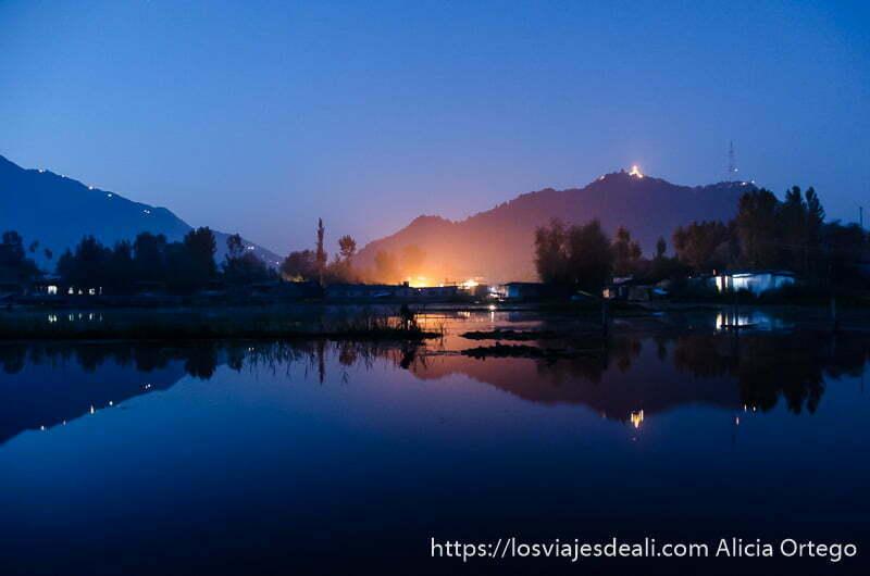 lago dal de noche con luz rojiza y montañas al fondo srinagar
