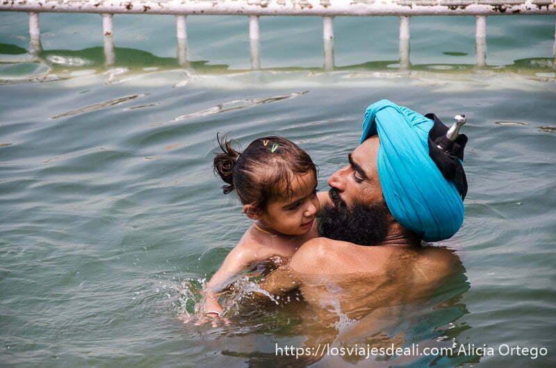 un padre bañándose con su hija pequeña en el lago sagrado del templo dorado de los sijs