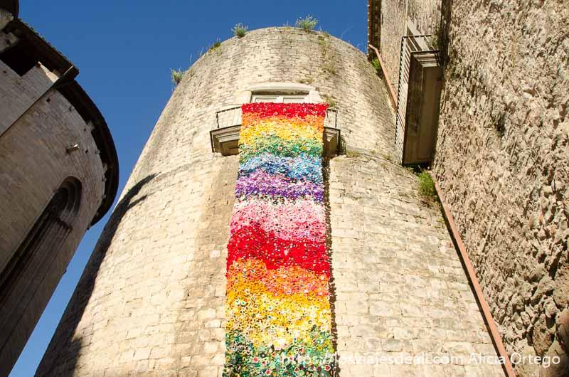 estela de flores de ganchillo muy larga colgada de una torre temps de flors