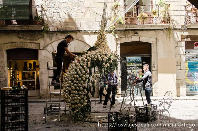 dos chicos preparando una escultura con cebollas, en forma de cebolla en el temps de flors