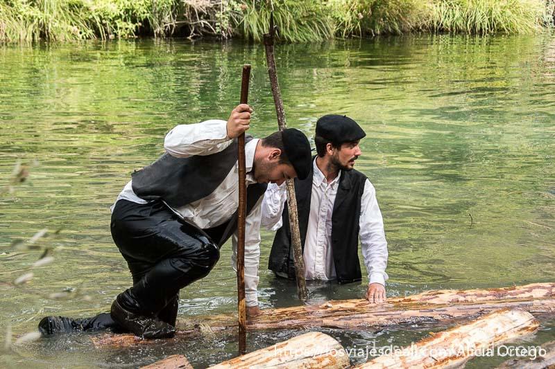 gancheros del alto tajo subiéndose a un tronco en el agua