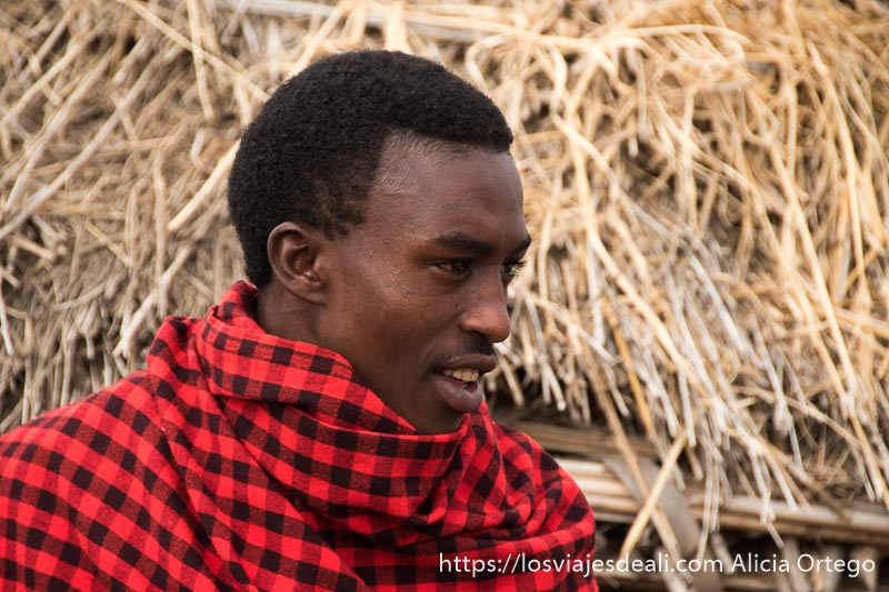 joven de la tribu masai con manta de cuadros roja
