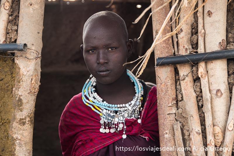 chica de la tribu masai con cabeza afeitada en la puerta de su casa