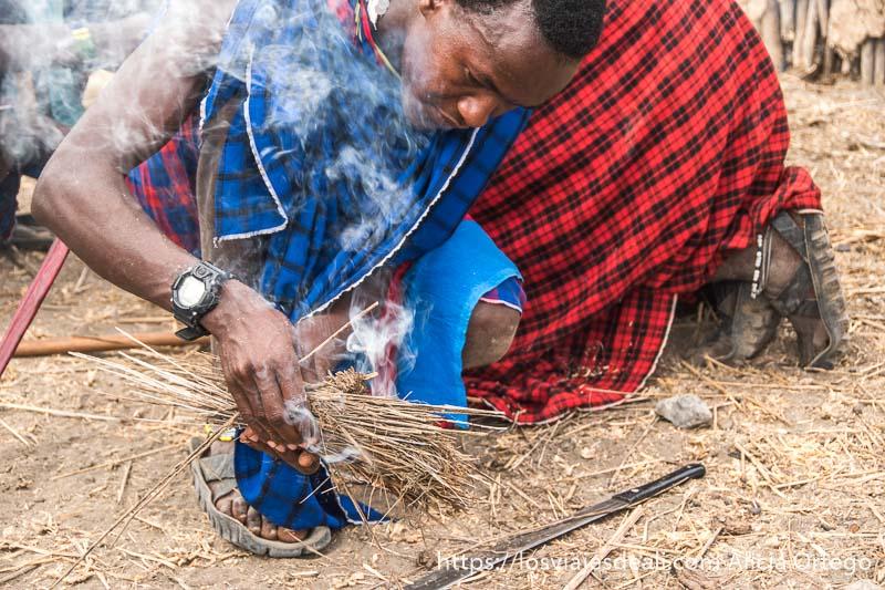joven de tribu masai haciendo fuego con dos palitos