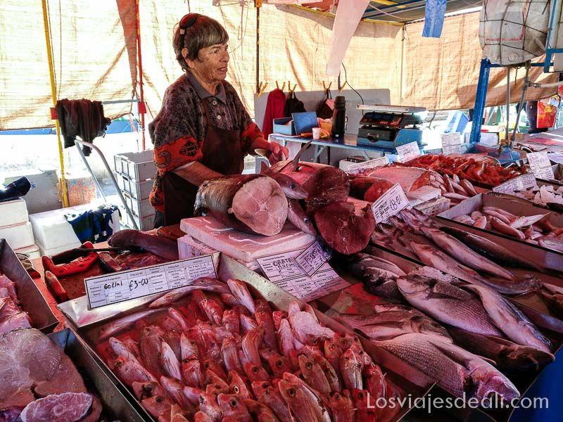 puesto de pescado con señora atendiendo en Marsaxlokk mercados del mundo