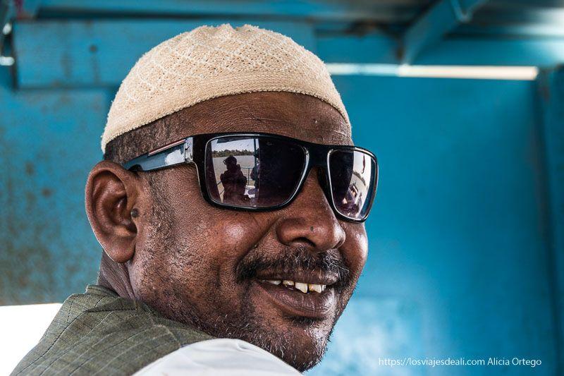 conductor de un ferry que cruza el Nilo con sus enormes gafas de sol y una gran sonrisa guía de viaje a Sudán