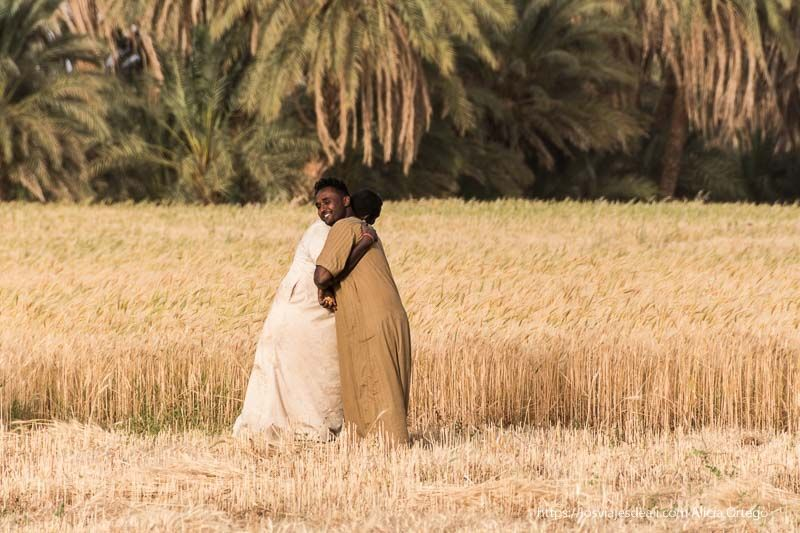 dos hombre se abrazan en un campo de trigo gentes de Sudán