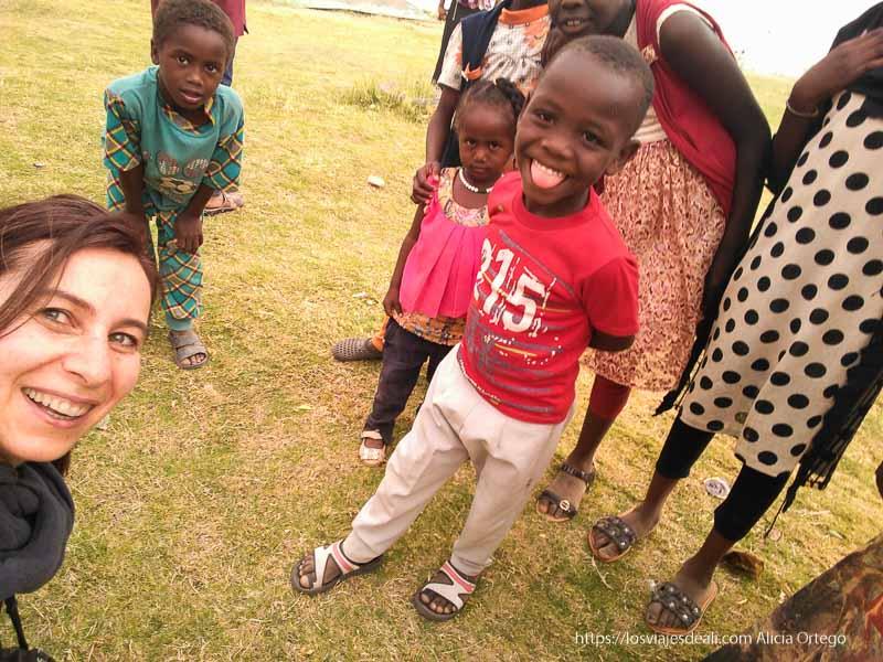 selfie con tres niños de Sudán. Uno de ellos sacando la lengua. Portada de las guías de viaje a África