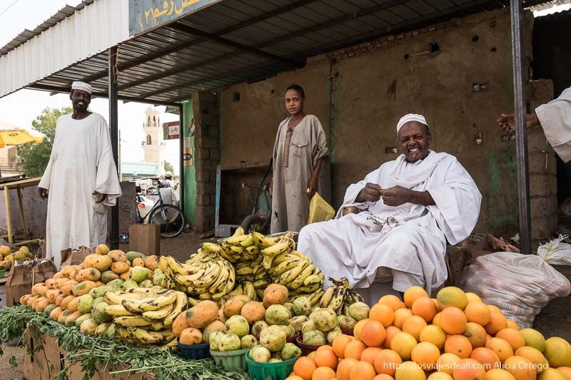 puesto de frutas con dos hombres sonrientes y una mujer gentes de sudán