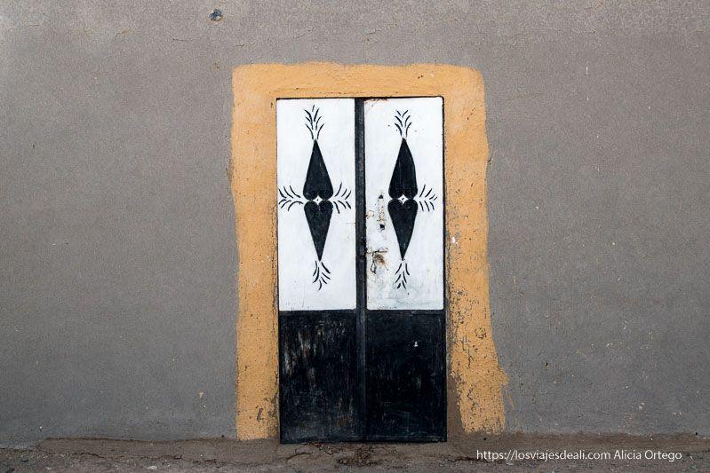 puerta de casa nubia pintada con colores y dibujos de palmeras
