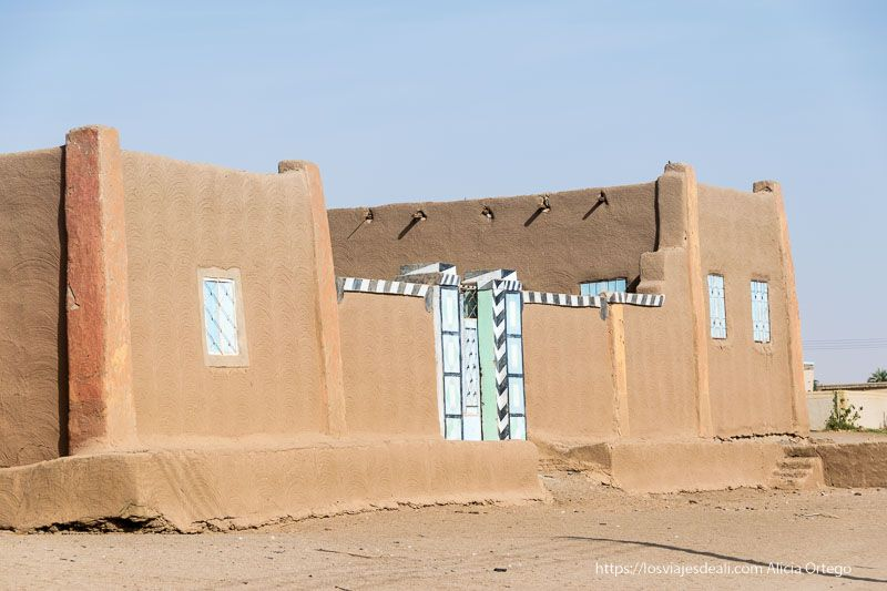 casa nubia de adobe con puertas y ventanas de color azul y verde