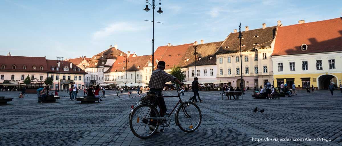plaza de sibiu con ciclista delante primeras impresiones de un viaje a transilvania