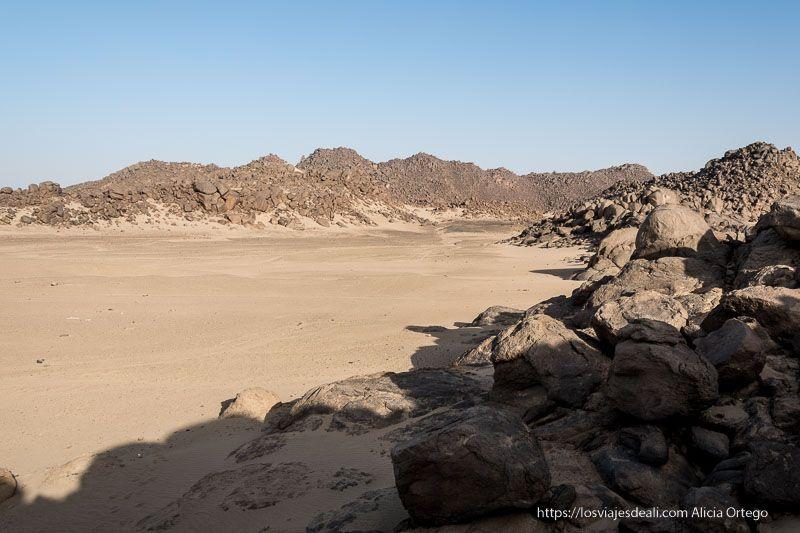 paisaje desértico con arena y rocas volcánicas redondeadas