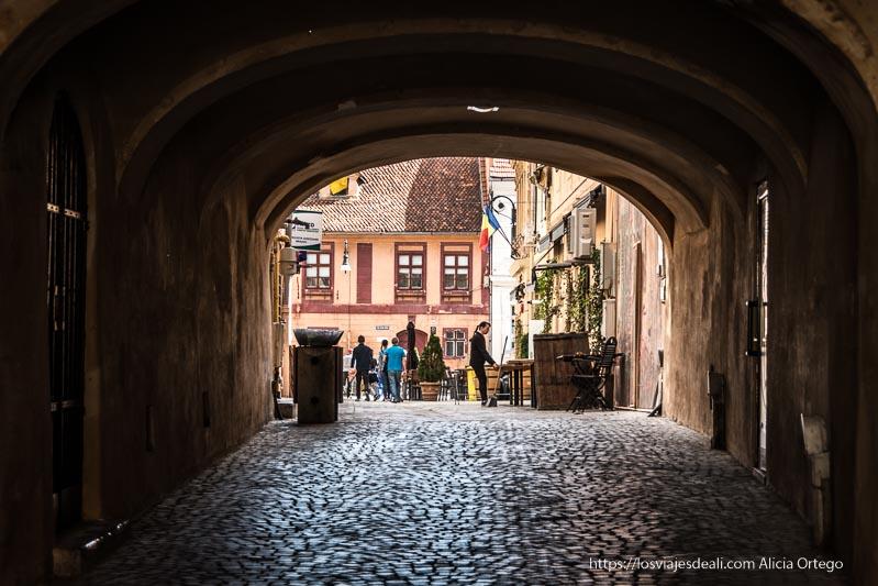 pasaje con arcos y calle adoquinada en Brasov Rumanía