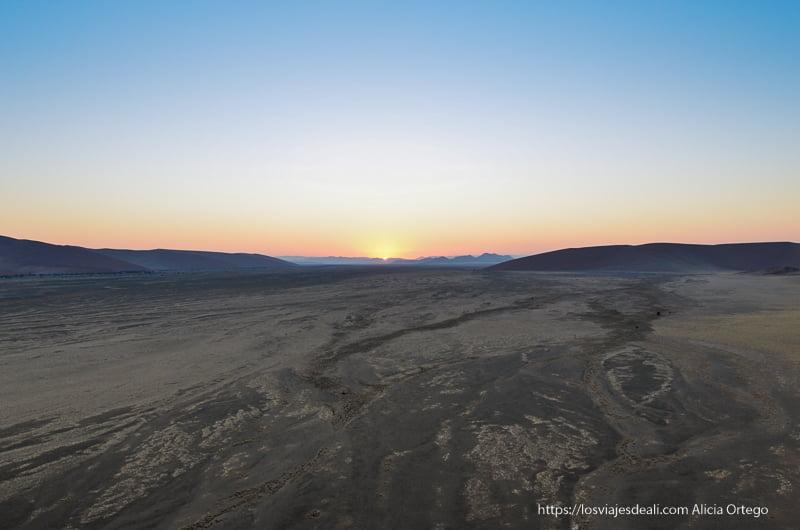 el sol comienza a salir en el horizonte del desierto de Namibia