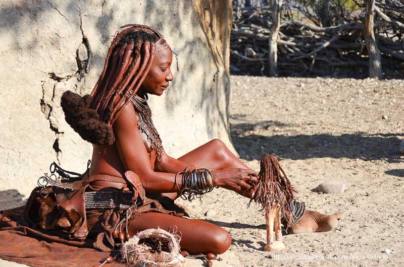 mujer himba haciendo artesanía en Namibia
