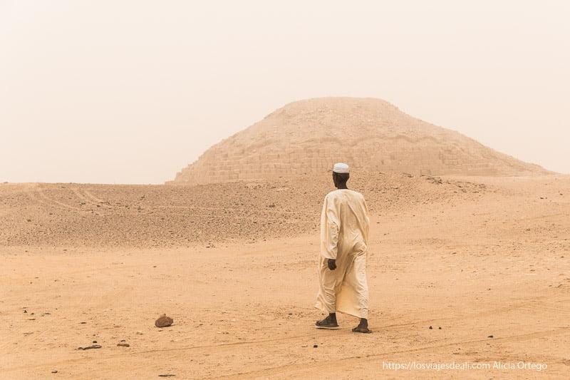 un hombre camina hacia la pirámide de El Kurru en Sudán
