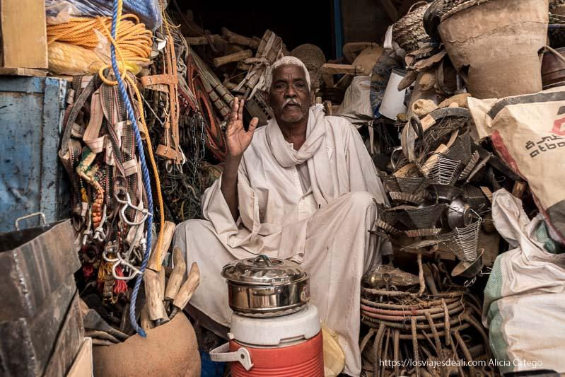 tendero de karima saludando rodeado de sus mercancías gentes de sudán