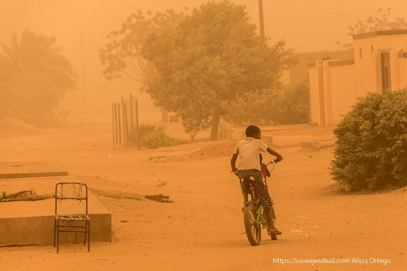 un niño va en bicicleta por la calle bajo la gran tormenta de arena