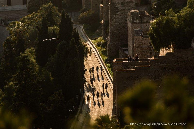 camino junto a la alcazaba con gente andando a contraluz