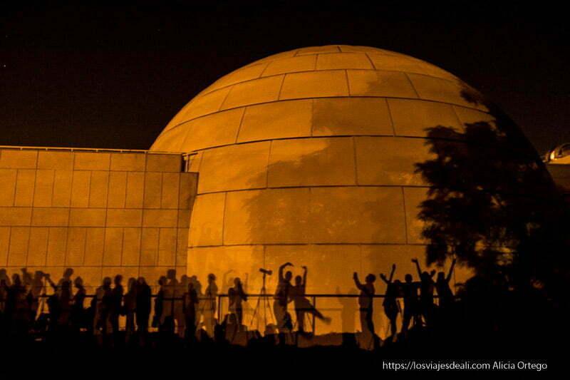 sombras de gente recortadas sobre la cúpula del planetario de Madrid en el eclipse de luna 2018