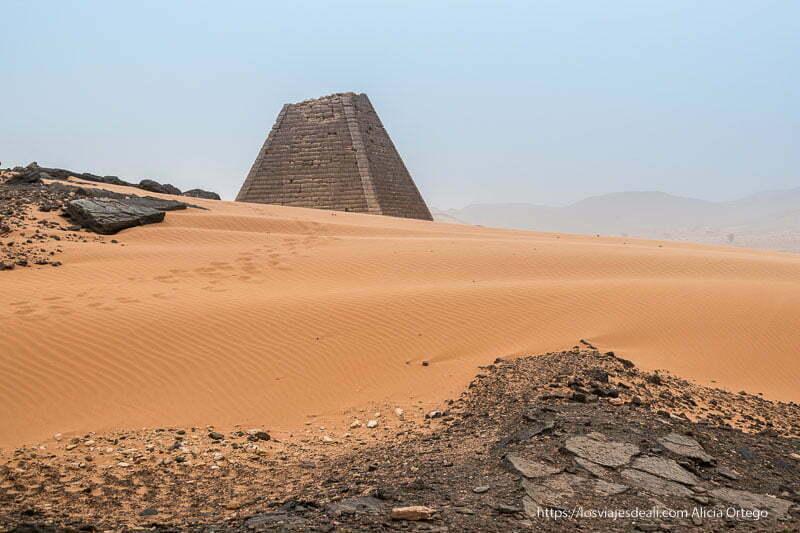 una de las pirámides de Meroe asoma detrás de la arena