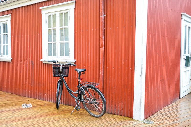 bicicleta junto a pared de chapa roja en Reykjavik