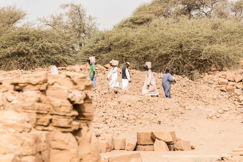 trabajadores de la royal city of Meroe llevando cestas con escombros en el hombro