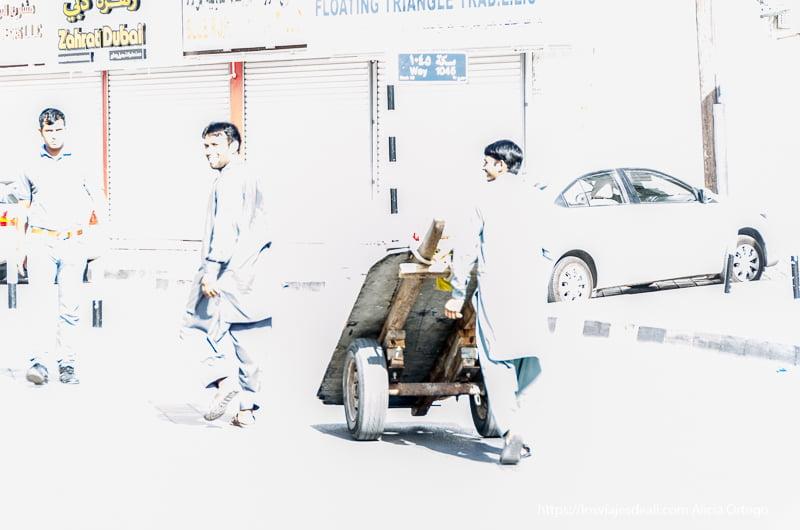 trabajadores indios de muscat llevando una carretilla