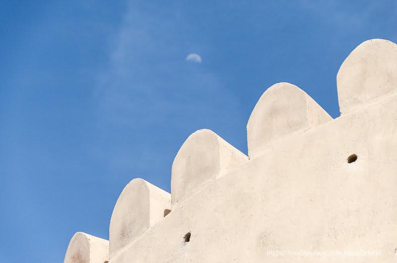 almenas de una torre antigua sobre cielo azul con luna en Muscat