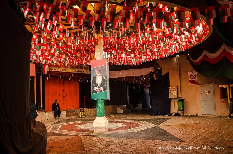 zoco de Muscat decorado con fotos del sultán y banderas