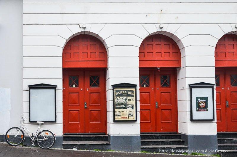 teatro con puertas rojas y una bici blanca apoyada en la pared en reykjavik
