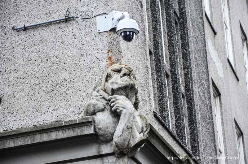 escultura en una fachada de reykjavik mirando a una cámara de seguridad