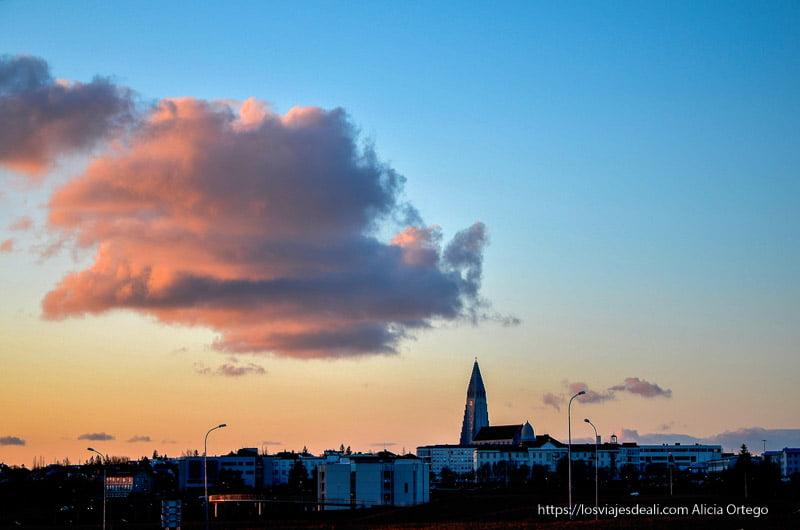 atardecer en Reykjavik con cielo azul y una gran nube roja sobre la catedral
