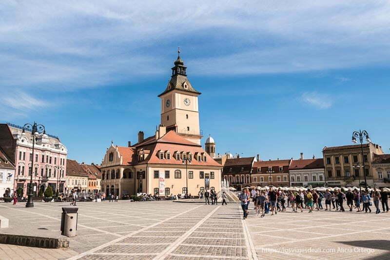 plaza sfatului con turistas cruzándola en fila y el antiguo ayuntamiento al fondo dos días en brasov
