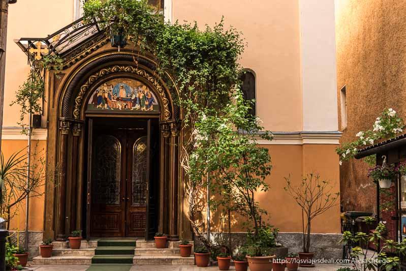 patio de iglesia ortodoxa con plantas alrededor de la puerta en brasov