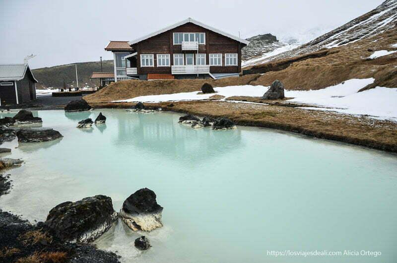 laguna termal de agua verde y hotel de madera