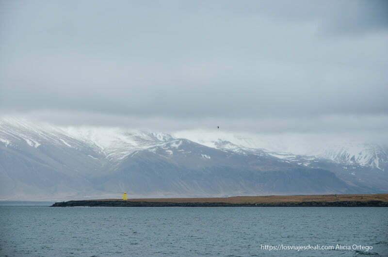 paisaje cerca de Reykiavik con altas montañas nevadas y un faro amarillo en una isla