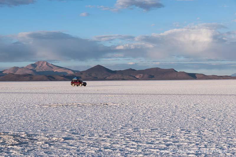 coche rodando sobre salar de uyuni con montañas al fondo resumen de un gran año de viajes