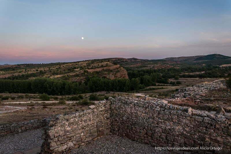 muros de las antiguas casas romanas de tiermes al atardecer con la luna al fondo