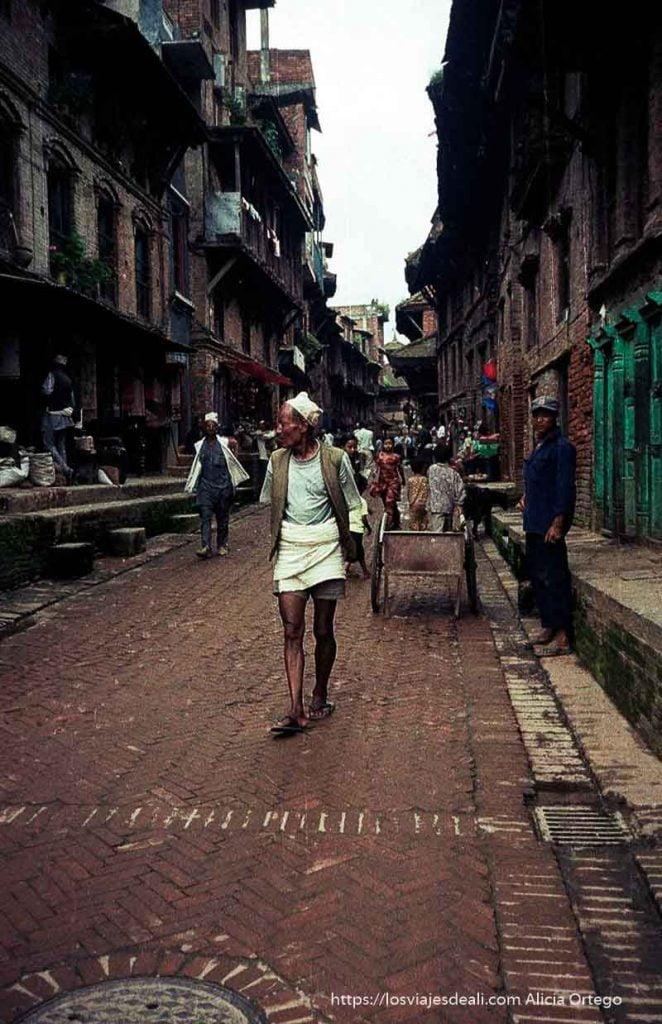 calle de baktapur con hombre andando hacia la cámara vestido tradicional nepal