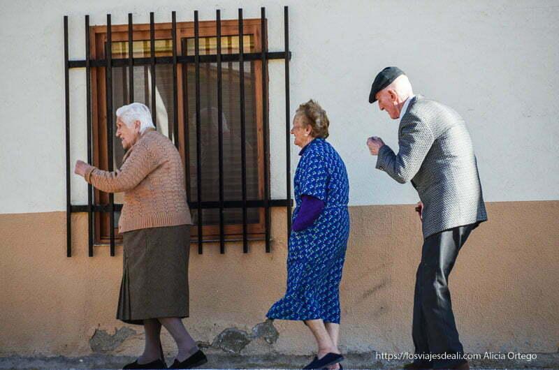 tres ancianos paseando en fila en un pueblo de campos de castilla