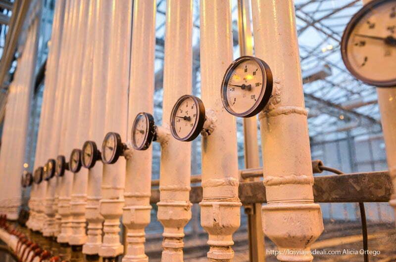 instalación geotérmica con grandes tubos de metal y manómetros que regulan el calor del invernadero
