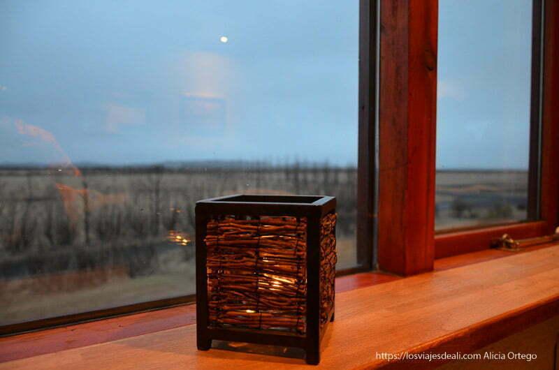 farolillo frente a la ventana frente al campo islandés