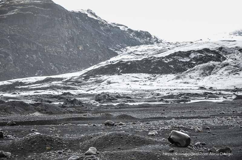 grandes rocas pulidas de color negro con el glaciar detrás