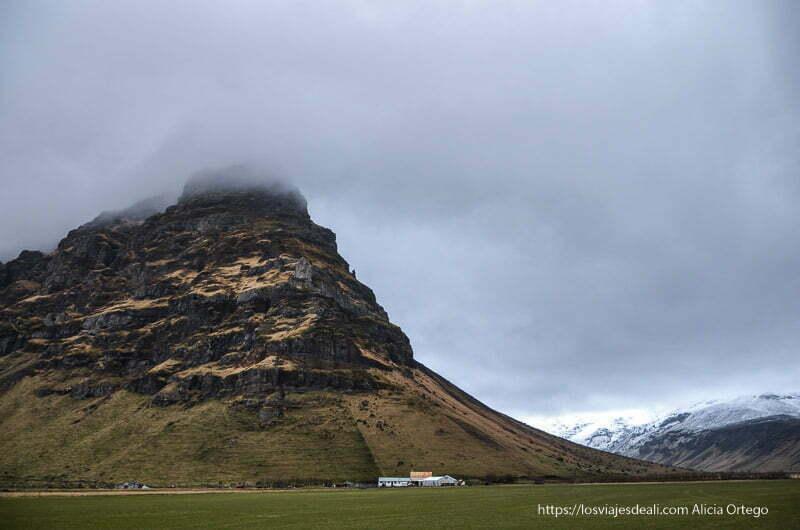 gran montaña con forma de cuña y prado verde con granja a sus pies