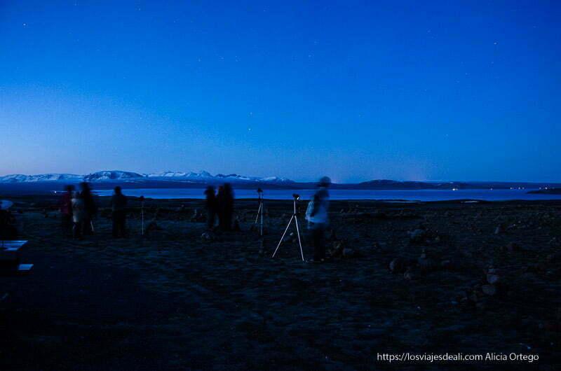 equipo con trípodes en el campo fotografiando auroras boreales en islandia